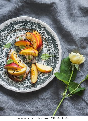 Sandwich with goat cheese and peach on a vintage plate on a gray background top view