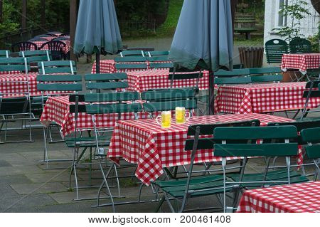 Two large beer jugs on a beer garden table with red white tablecloth and green wooden chairs in a public beer garden.