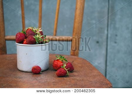 Berries strawberries in a metal cup on an old chair in the country