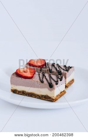 A useful raw dessert made of nuts and dried fruits from currant mousse adorned with strawberries