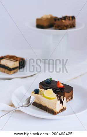 Assortment of useful raw desserts with dried fruits and nuts on a white background