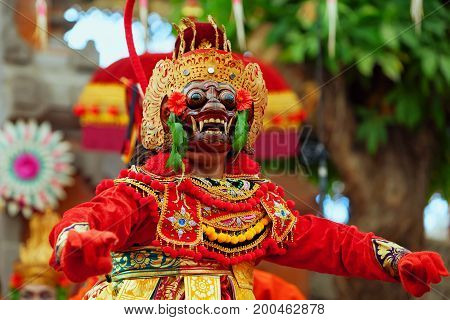 Dancer man in traditional Balinese costume and monkey mask - character of Bali island culture. Temple ritual dance at ceremony before religious holiday. Ethnic festivals arts of Indonesian people.