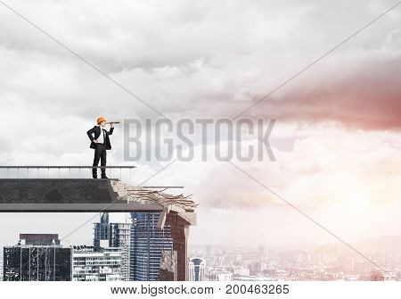 Young engineer in suit and helmet looking in spyglass while standing on broken bridge with cityscape and sunlight on background. 3D rendering.
