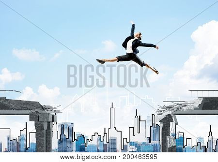 Business woman jumping over gap in concrete bridge as symbol of overcoming challenges. Cityscape on background. Mixed media.