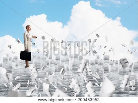 Confident business woman in suit standing on pile of documents among flying papers with cloudly skyscape on background. Mixed media.
