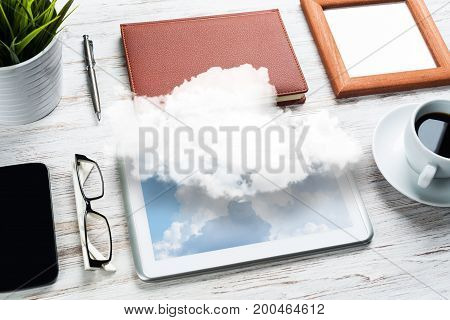 Top view of modern workplace with office stuff and cloud above presenting still office life. Mixed media.