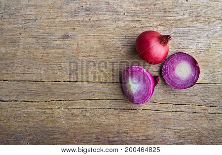 Onions on wooden table. Spicy onions on wooden background