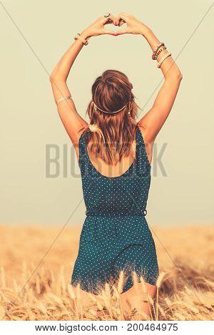 Girl making a heart-shape in a wheat-field.