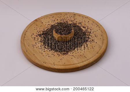 Healhty chia seeds spilling out of wooden bowl on wooden plate