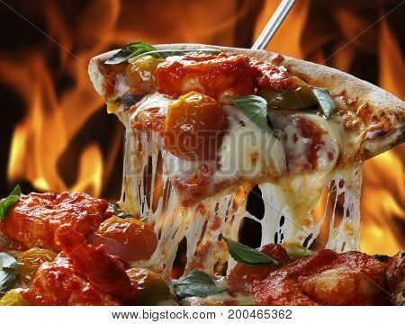 Slice of pizza raised with wood oven in the background