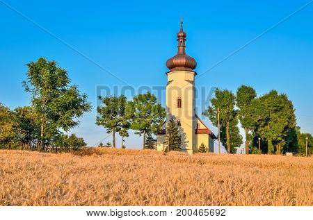 Beautiful church on a picturesque hill. The historic baroque church of St. Clement in Ledziny Poland.