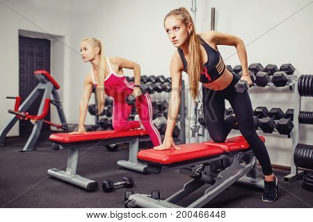 Fitness girls lift dumbbells in the gym on the bench. Concept team sports with friends.