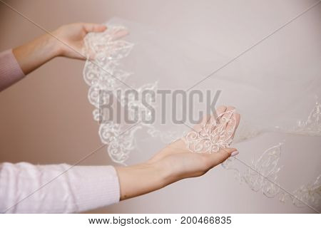 Close-up of a girl showing veil a narrow, wide braid and lace figure. The concept of choosing wedding accessories for the bride.