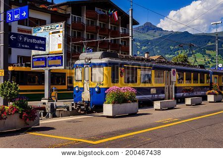 Grindelwald Bernese Oberland Switzerland - AUGUST 1 2017 : Yellow - Blue train from the Berner Oberland-Bahn to Interlaken in the Grindelwald railway station