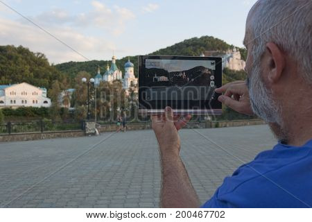 A man holds a tablet in his hands and photographs the landscape