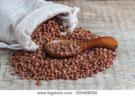 Buckwheat groats on a wooden background with a spoon