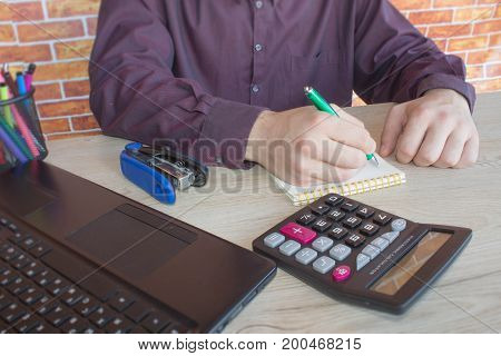 Close up of male hands on her calculator's keyboard. The second hand in on the touchpad. Concept of accountant's work. Businessman using a calculator to calculate the numbers