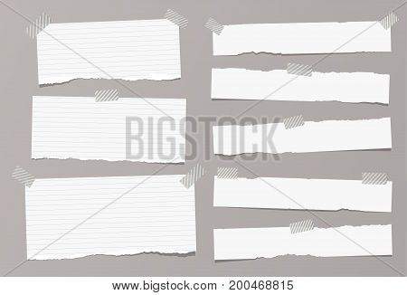 White ripped ruled, lined note, copybook, notebook paper strips stuck with sticky, adhesive tape on grey background