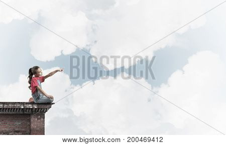 Cute kid girl sitting on top and pointing at something