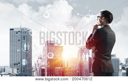Young elegant businessman with hand on chin looking away