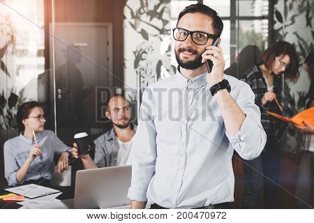 Сlose Up Photo Of Smiling Bearded Businessman Wearing Glasses While Talking On Smartphone With Custo