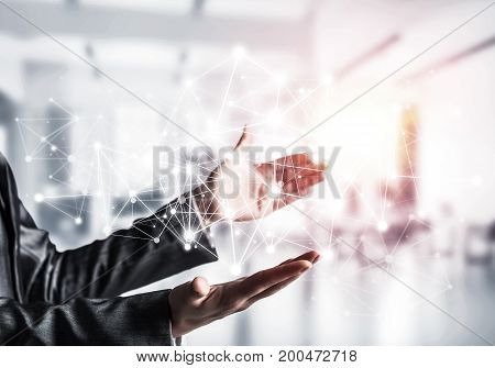 Business woman in suit keeping white social media network structure in hands with sunlight and office view on background. Mixed media.