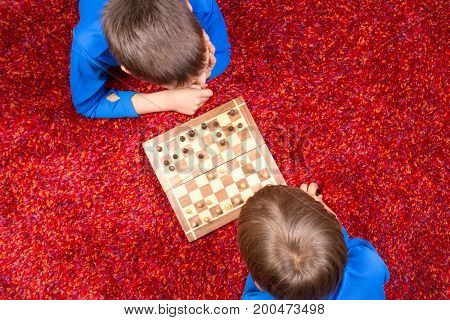 Two boys lying on the floor and playing chess at home