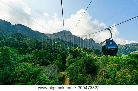 Ropeway leading to tree covered hills, fog and cloudy skies. Beautifully shot in Langkawi