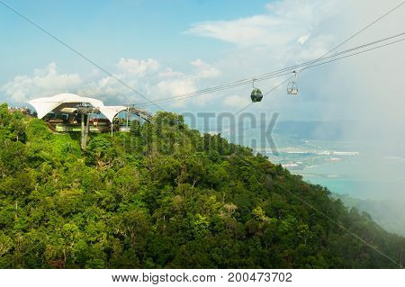 Beautiful ropeway station atop a tree covered mountain with the sea in the distance, fog rolling in and cloudy skies. Shot in Langkawi, Malaysia