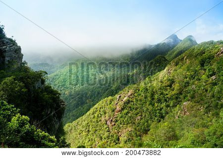 Beautiful tree covered mountains fading into the distance with cloudy skies and fog rolling between them. Shot in Langkawi near the Machincang mountain