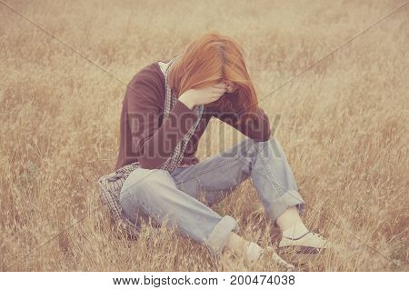 Lonely sad red-haired girl at autumn meadow