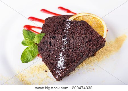 piece of chocolate cake on a plate decorated with berry topping mint and slice of lemon