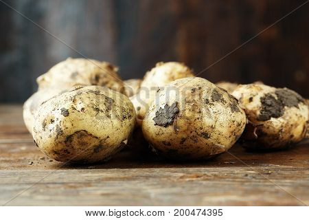 pile of young potatoes on a dark brown wooden background space for text