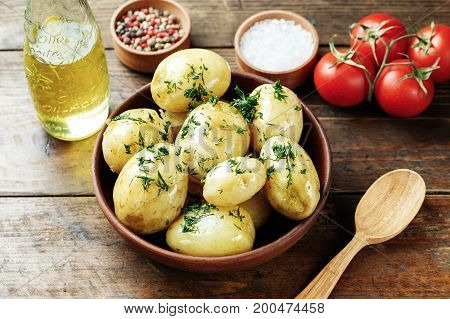 Boiled young potatoes in a plate on a wooden table next to lie fresh vegetables space for text
