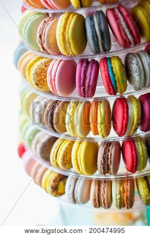 Sweet sandwich-biscuits different colors,  nicely stacked in a row in a circle in a pyramid on display in the store.