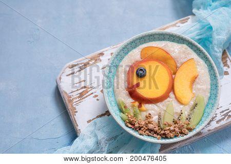 Kids breakfast oatmeal porridge with fruits look like cute fish