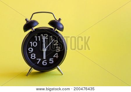 Alarm clock with six o'clock on yellow background in minimalistic retro pop art style with place for text. Wake up concept. Back to school. Copy space.
