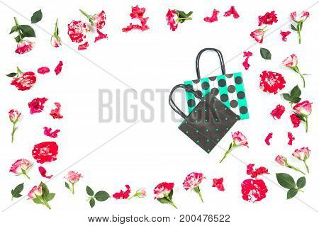 Colorful paper shopping bags and rose flowers frame on white background. Top view