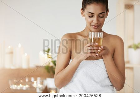 Tender african girl in towel smiling holding glass with tea resting in spa salon. Closed eyes.