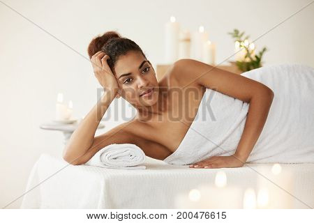 Young beautiful african girl in towel smiling relaxing resting in spa salon.