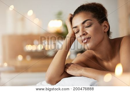 Portrait of young tender african girl with closed eyes resting relaxing in spa resort.