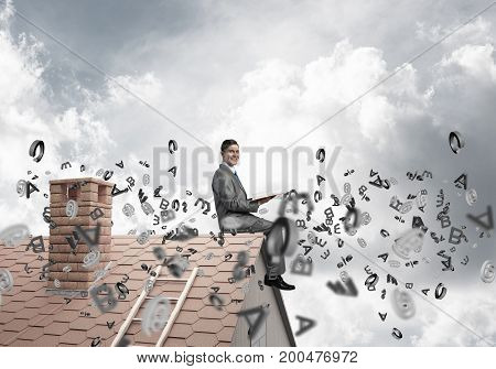 Young businessman sitting on house with red book in hands