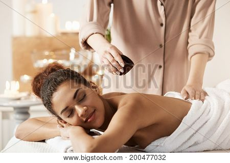 Masseur pouring oil doing massage for young beautiful african girl in spa salon.