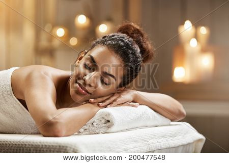 Young beautiful african girl resting relaxing in spa resort with closed eyes.