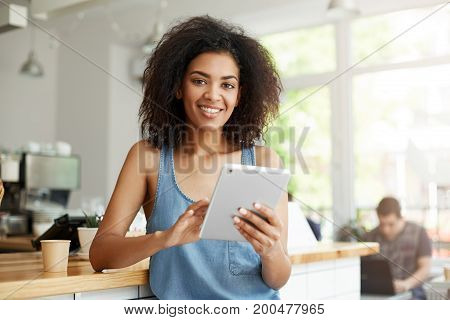 Young beautiful happy african girl resting in cafe smiling looking at camera holding tablet. Copy space.