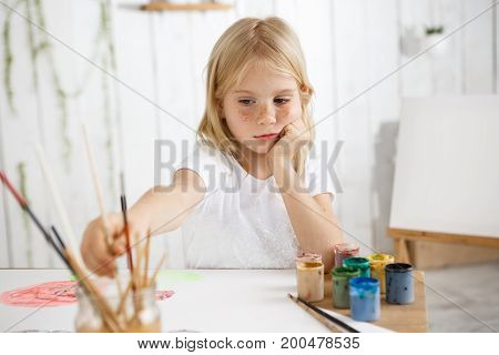 Creative seven-year-old girl busy painting watercolors, sitting at the table and putting her elbows on the table, rested her head in her hands, thinking about her picture. Little female child with blonde hair and freckles wearing white t-shirt, sitting at