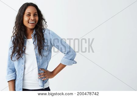 Close up of attractive smart-looking smiling dark-skinned female model posing isolated on white background. Cheerfully smiling with teeth beautiful woman with dark skin and long wavy hair dressed casually.