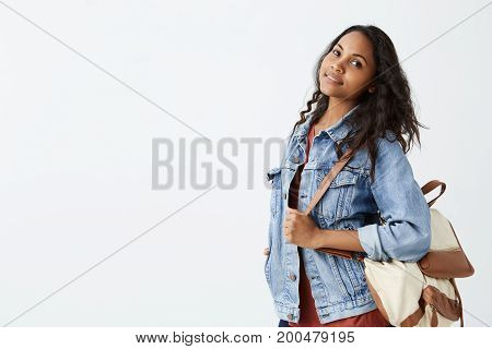 Beautiful positive friendly-looking young Afro-American woman with dark wavy hair lovely smiling in denim jacket and red t-shirt with rucksack on her shoulder posing on background of white studio wall.