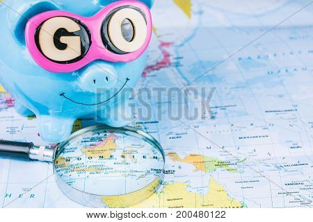 Going to Travel. Magnifier laying on the map. Saving piggy bank with sunglasses and GO slogan staying on the world map.