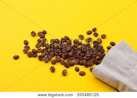 Burlap sack full of coffee beans on yellow background